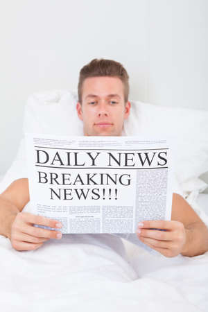 Young Man Reading Breaking News On Newspaper Stock Photo - 21668774