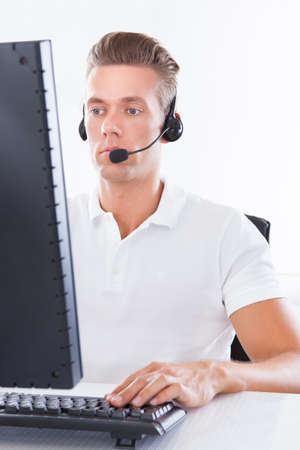 life support: Photo Of Young Man With Headset Using Computer Stock Photo