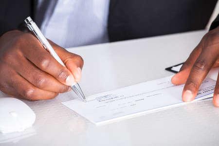 bank overschrijving: Close-up Van Menselijke Hand Schrijven Op Cheque