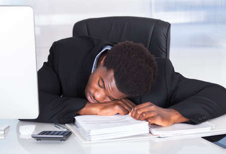Portrait Of Stressed Businessman Sleeping In Office photo