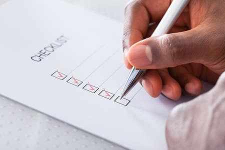 チェック ボックスをマーク赤ペンを持つ手のクローズ アップ 写真素材