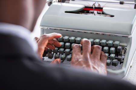 Portrait Of Happy Business Man Typing On Typewriter Banco de Imagens