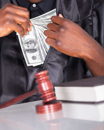 Male Judge Putting Some Money In His Pocket In A Courtroom photo