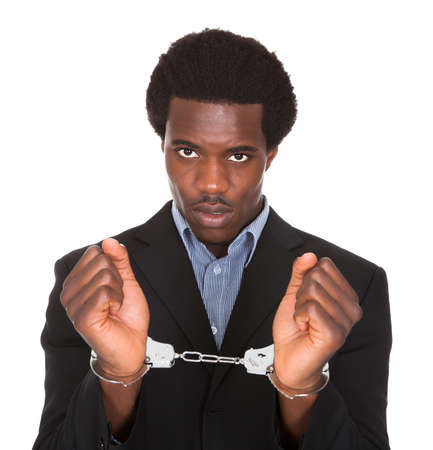 handcuffed hands: Young African Man With Handcuffed Hands Isolated On White Background
