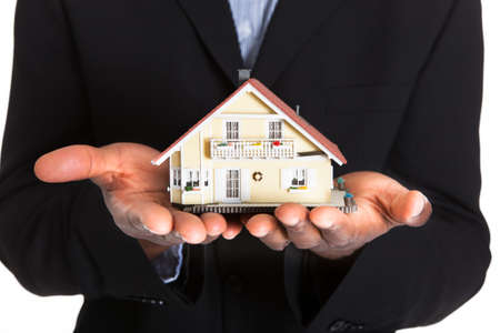 hand holding house: Young African Businessman Holding House Model Isolated Over White Background