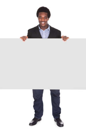 Happy African Businessman Standing On White Background Looking At Placard photo