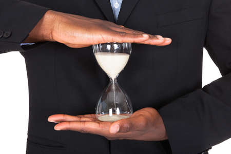 african businessman: Close-up Of African Businessman Holding Hourglass In Hands Stock Photo