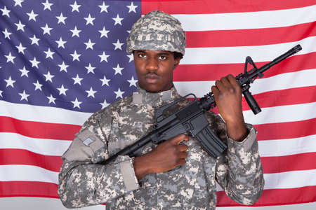 African American Soldier Standing With Gun Standing In Front Of Us Flag photo