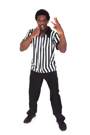 Portrait Of An African Referee Gesturing Over White Background photo