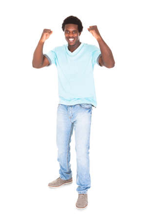 clenching fists: Excited Casual Young African Man Clenching His Fist Isolated Over White Background