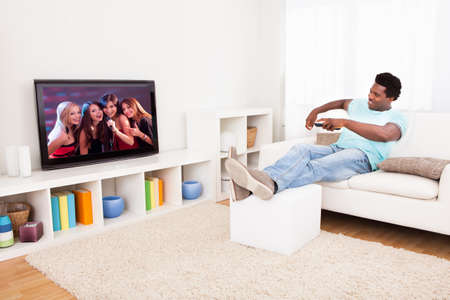 Happy African Young Man Watching Television At Home photo