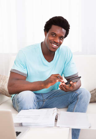 taxes budgeting: Happy African Young Man Calculating His Finance Expenses At Home Stock Photo
