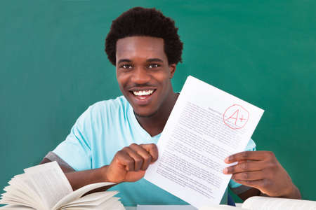 test result: Happy African Male Student Showing A Paper With Perfect Grade A Plus In Classroom