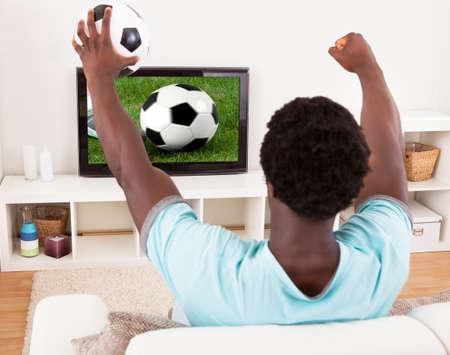 personas mirando: Feliz Joven africana Ver partido de fútbol en la televisión en casa