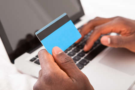 Young African Man Holding Credit Card And Using Laptop For Online Shopping photo