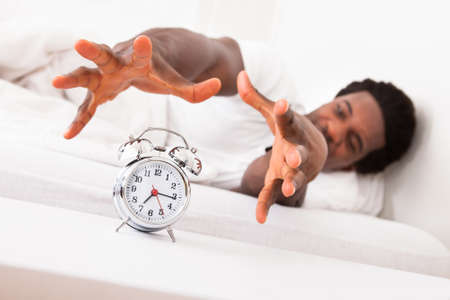 Frustrated Man Trying To Catch Is Alarm Clock While Relaxing On His Bed Stock Photo