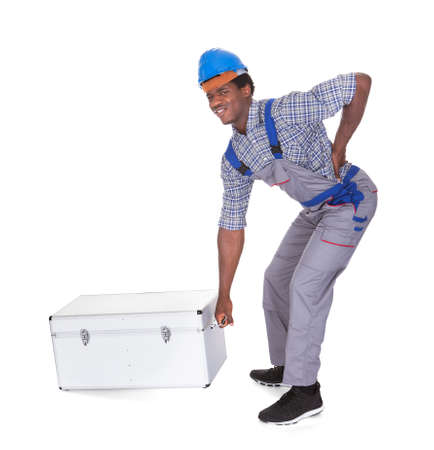 Young African Man With Back Pain Lifting Metal Box Isolated On White Background photo
