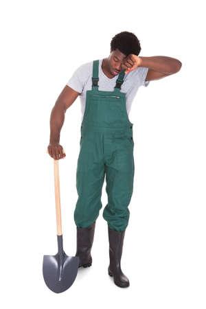 Tired Male Gardener Holding Shovel Over White Background photo