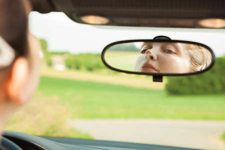 Young Woman Looking At Mirror While Driving The Car