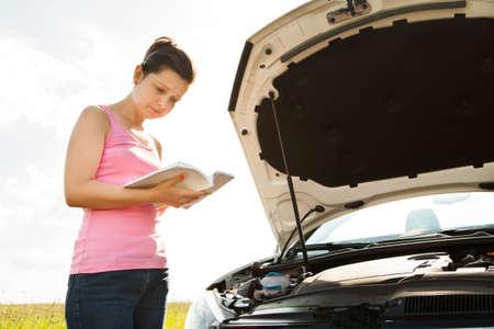 instructions: Giovane donna leggendo il libro sul davanti auto con Aperto Hood