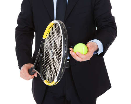 Businessman Holding Tennis Racket And Ball Over White Background photo