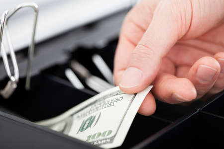 cash box: Close-up Of Hand With Dollar Notes Over Container Stock Photo