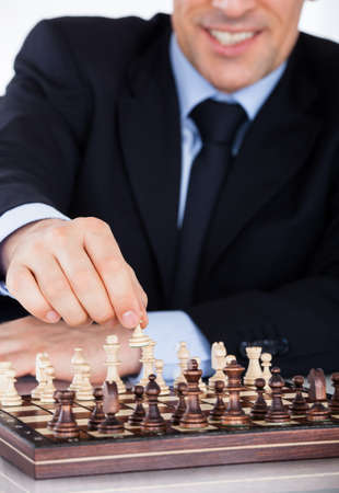 Portrait of a mature businessman playing chess photo