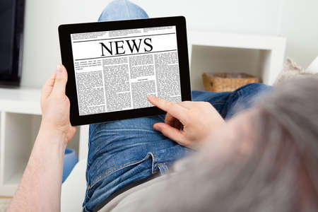 Close-up Of a Mature Man reading news on digital tablet Stock Photo