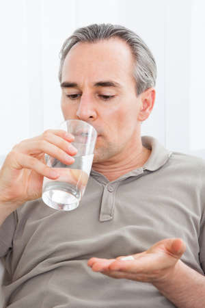 Ill man taking medication sitting up holding a glass of water looking at a tablet in her hand