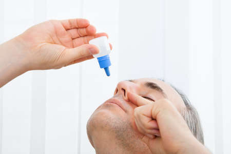 Close-up of a man using nasal spray; indoors photo