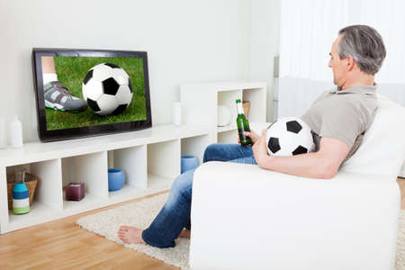 Portrait of a mature man watching football on television photo