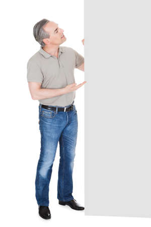 Happy Mature Man Standing Behind Placard isolated on White Background photo