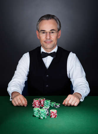 croupier: Portrait of a croupier with gambling chips on table
