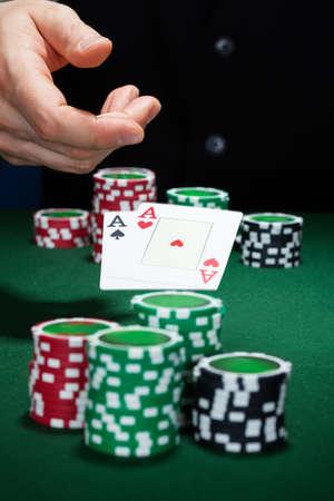 croupier: Close-up of hand with playing cards and gambling chips