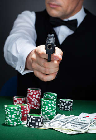 croupier: Croupier with stack of token chips and banknote on table aiming with a gun