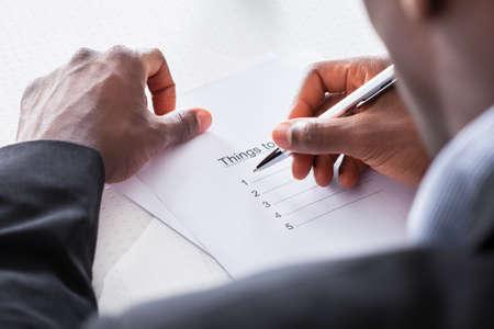 hacer: Primer plano del hombre de negocios Planificación de mano para hacer la lista