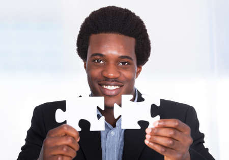 entrepreneurs: Portrait Of A Happy Young Businessman Holding Jigsaw Puzzle Stock Photo