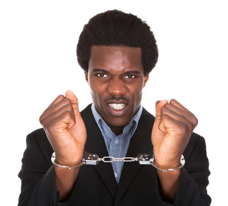 sequester: Young African Man With Handcuffed Hands Isolated On White Background