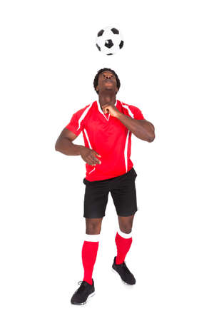 american football ball: Portrait Of African Soccer Player Playing With Football Over White Background