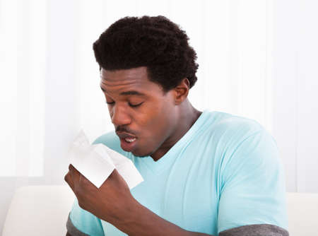facial tissue: African Young Man Having A Cold Holding Tissue And Blowing His Nose