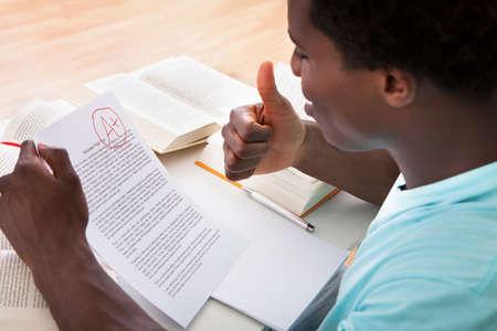 Gelukkig Afrikaanse Mannelijke Student Met Een Papier Met Perfect Grade A Plus in de klas
