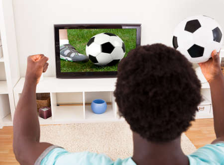 Happy African Young Man Watching Football Match In Television At Home photo