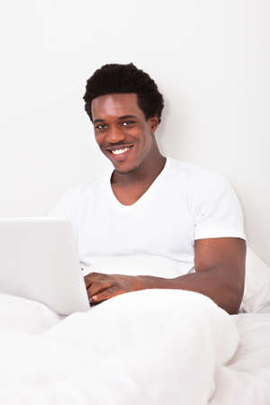 Happy Young African Man Using Laptop Sitting On Bed In Bedroom Stock Photo - 21870474
