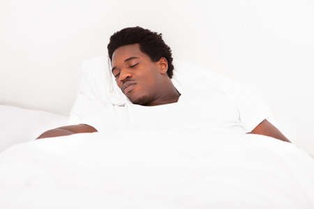 Handsome Young African Male Sleeping In Bed At Home Stock Photo - 21864257