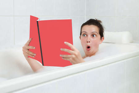 Portrait of happy young woman in bathtub reading book photo