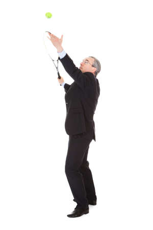 innings: Mature Businessman Holding Tennis Racket And Ball Over White Background