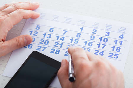 important people: Close-up Of Hand Holding Pen Over Calendar With Mobile Phone Stock Photo