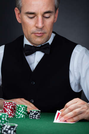 croupier: Close-up of a hand of poker player with cards and chips Stock Photo