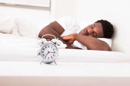 an alarm clock: Joven dormir africano masculino en la cama delante de despertador Foto de archivo