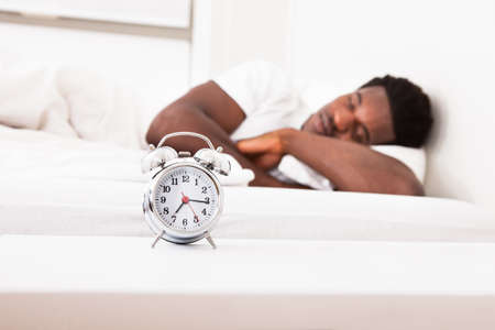 Young African Male Sleeping On Bed In Front Of Alarm Clock photo